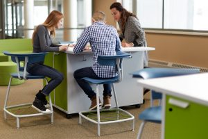 Students engage with teacher sitting at KI Ruckus Work Table in Ruckus Stools
