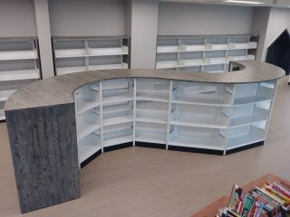 Low height, library bookcases that are curved for an interesting aesthetic